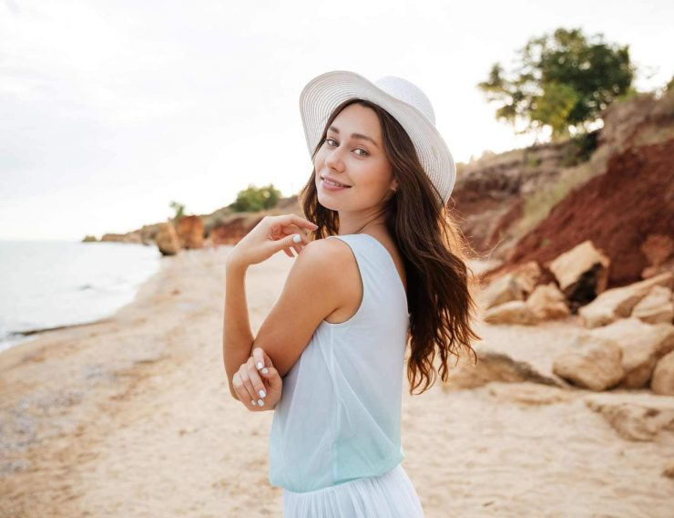 happy-young-woman-in-white-hat-waalking-near-the-PMPGEFG.jpg